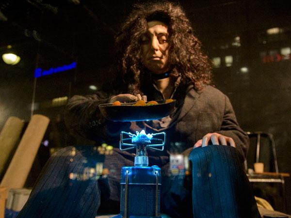 La Revolte des Mannequins: Schaufensterpuppe als Obdachloser kocht sein Essen überm Gasbrenner