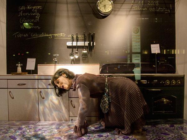 La Revolte des Mannequins: Schaufensterpuppe beim Schubben des Küchenbodens